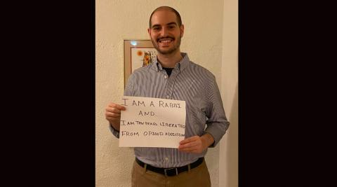 """Rabbi Michael Perice smiling and holding a small sign that says, """"I am a rabbi and ... I am ten years liberated from opiod addiction."""""""