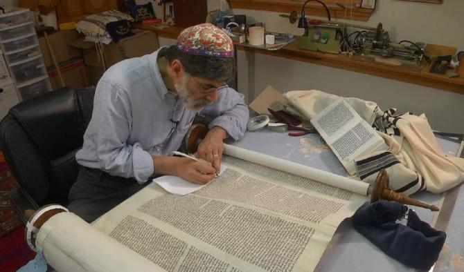 """Northampton Rabbi Kevin Hale, a sofer, or Torah scribe, works on a scroll in his Leeds office in a scene from """"Commandement 613."""""""